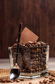 Glass pot with coffee beans and chocolate — Stock Photo