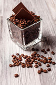 Ein quadratischer behälter mit kaffeebohnen und schokolade — Stockfoto