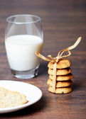 Five cookies with a ribbon and milk — Stock Photo