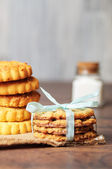 Some cookies with a ribbon on linen and wood — Stock Photo