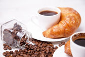 A white cup of coffee and croissants — Stock Photo