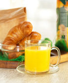 Orange juice in a transparent mug with pastries on the backgroun — Stock Photo