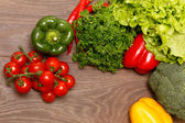 Tomatoes, paprika and other vegetables on a wooden surface — Stock Photo