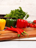 Chilli peppers and bell peppers on a board — Stock Photo