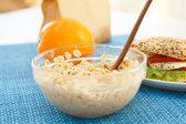 A big bowl of oat porridge and a sandwich — Stock Photo