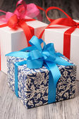 Three pretty gift boxes on a wooden surface — Stock Photo