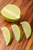A lime and three slices on a wooden surface — Stockfoto