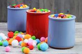 Tres frascos con caramelos coloridos y perlas de fieltro — Foto de Stock