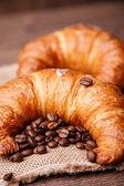 Dos medialunas y granos de café en una servilleta de lino — Foto de Stock