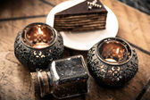 Kerzen und tee mit einem schokoladenkuchen — Stockfoto