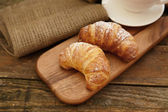 Two croissants with powder sugar on a wooden board — Stock Photo