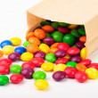 Colorful chocolate candies in a paper bag — Stock Photo