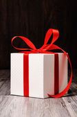 A white box tied with a red ribbon — Stock Photo