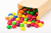 Kolorowe cukierki czekoladowe w papierowej torebce — Zdjęcie stockowe