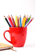 Colorful pencils in a red cup and a copybook — Zdjęcie stockowe