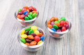 Three glass bowls with colorful crunchy treats — Stock Photo