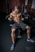 Tipo poderoso con dos pesas en el gimnasio — Foto de Stock
