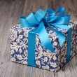 Blue patterned box with light blue ribbons — Stock Photo #41242419