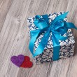 A square blue box with a bow and two hearts — Stock Photo
