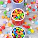 Постер, плакат: Three jars of colorful sweets and felt balls around