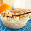 A bowl full of oatmeal and orange with a sandwich on the backgro — Stock Photo