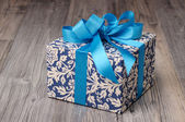 Blue patterned box with light blue ribbons — Stock Photo