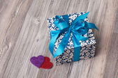 A square blue box with a bow and two hearts — Stockfoto
