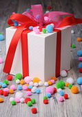 A white box with red ribbons and a lot of felt colorful balls — Stock Photo