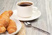 两个牛角面包板和一杯黑咖啡 — 图库照片
