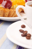 A fragment of a white cup with coffee beans and a tartlet — Stock Photo