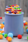 Three jars of crunchy candies and woolen felt balls around — Stock Photo