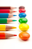 Coloring pencils pointing at candy pattern — Stock Photo