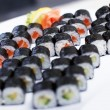 Five sushi sets on a white plate with ginger and lemon — Stock Photo
