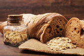 A loaf of crusty bread and a jar of oats — Stock Photo
