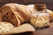 A loaf of crusty bread and a jar of oats — Foto de Stock