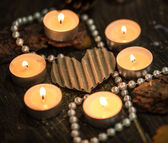 Six tea candles around a paper heart and pearls — Stock Photo