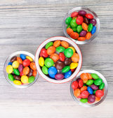 Four jars with multicolor crunchy candies — Stock Photo
