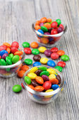 Three tiny bowls with crunchy color candies — Stock Photo