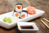 Three salmon sushi on a little plate — Stock Photo