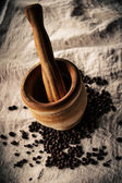 Wooden mortar and pestle and allspice on linen — Stock Photo
