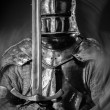 Knight in a full armor, holding a sword — Stock Photo