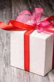 White gift box with a red ribbon — Stock Photo