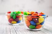 Two bowls with multicolor candies on a desaturated background — Stock Photo