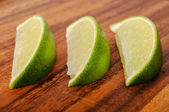 Three equal slices of lime on a wooden surface — Stock Photo