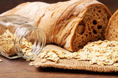 Oats and a loaf of bread on a napkin — Stock Photo