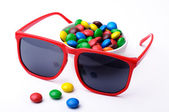 Red plastic sunglasses and a bowl of candies — Stock Photo