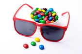 Isolated photo of red sunglasses and hard candies — Stock Photo