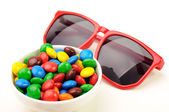 Red sunglasses and colorful candies — Stock Photo