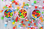 Multicolor candies in three jars and woolen balls around — Stock Photo