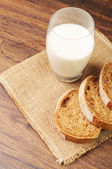 A glass of milk and bread slices on a napkin — Stock Photo